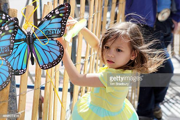 Jaslene Oyola of Boston MA affixes a butterfly to a memorial near the Boston Marathon finish line on Boylston Street commemorating the twoyear...