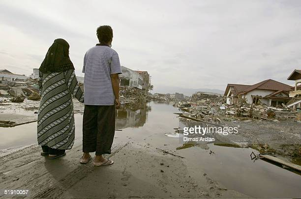 Jasmi and his wife Sunarti are seen holding hands in their former residential area that was leveled by Sunday's tsunami on January 3 2005 in Banda...