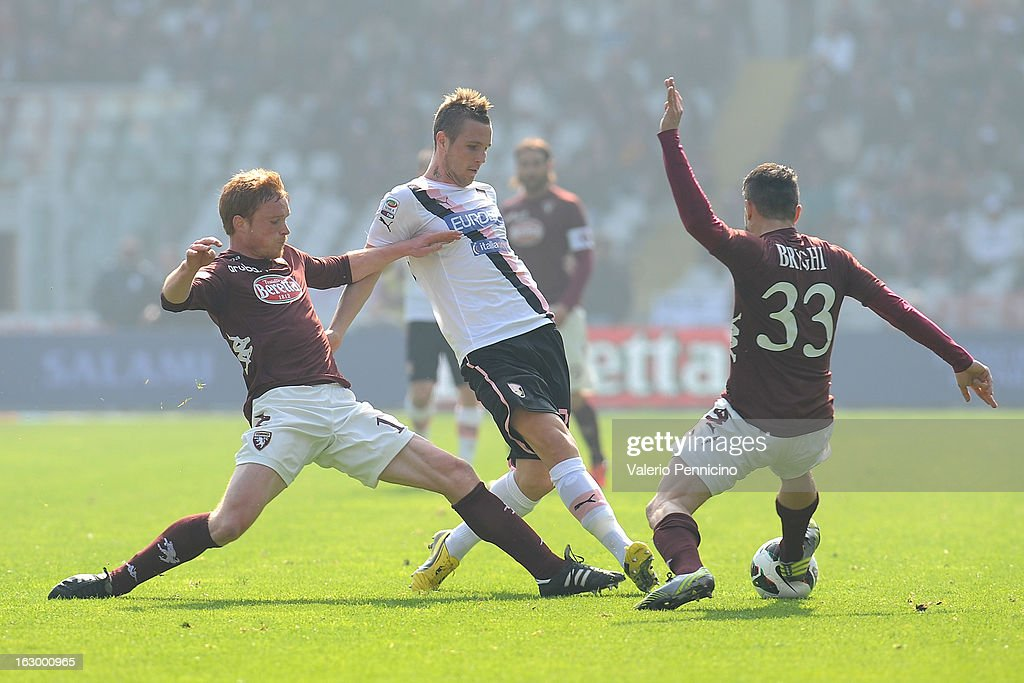 Jasmin Kurtic (C) of US Citta di Palermo is challenged by Matteo Brighi (R) and Alessandro Gazzi of Torino FC during the Serie A match between Torino FC and US Citta di Palermo at Stadio Olimpico di Torino on March 3, 2013 in Turin, Italy.