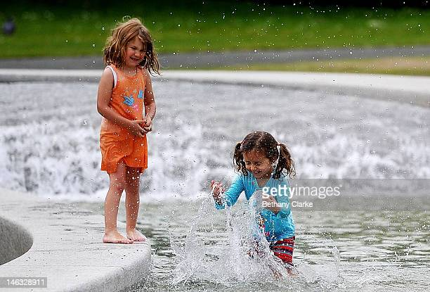 Jasmin Woolhouse and Arnica Albl both fouryearsold play in the Princess Diana Memorial fountain in Hyde Park on June 14 2012 in London England...