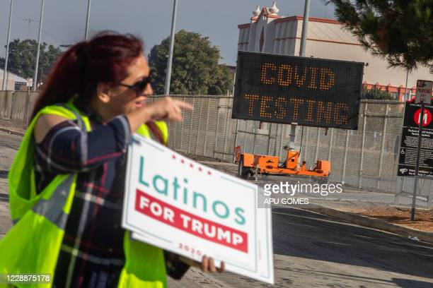 Jasmina Saavera holds a Latinos for Trump sign in front of a COVID-19 Testing place before a Pro-Trump car caravan start in Long Beach, California on...