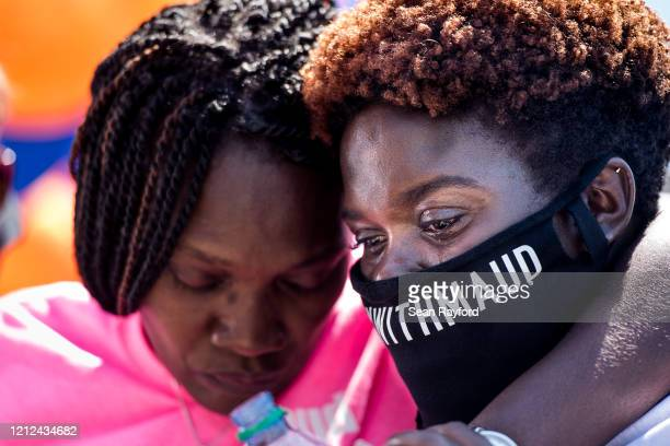 Jasmine Arbery sister of Ahmaud Arbery and Wanda CooperJones Ahmaud's mother comfort one another while people gather to honor Ahmaud at Sidney Lanier...