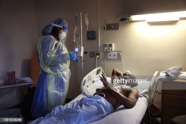 Jasmine Mitchell treats Curtis Jones with Remdesivir to help him recover from COVID-19 at Roseland Community Hospital on December 15, 2020 in...