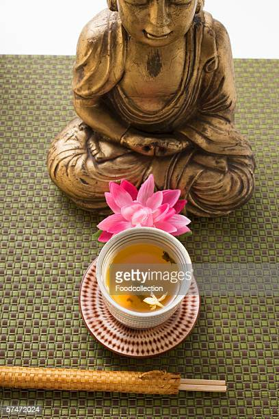 Jasmine tea in small bowl in front of Buddha