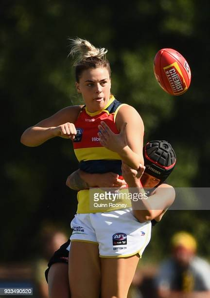 Jasmyn Hewett of the Crows handballs whilst being tackled during the round seven AFLW match between the Collingwood Magpies and the Adelaide Crows at...