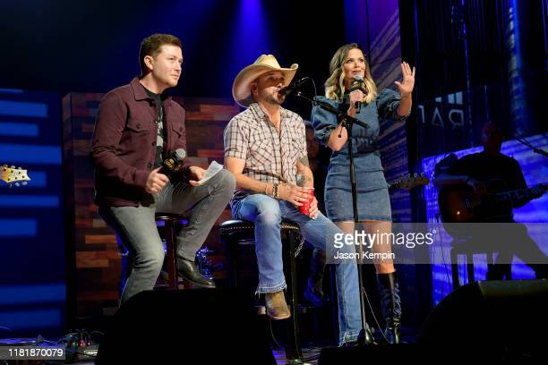 Jason Aldean and Amy Brown speak with host ScottyMcCreeryon stage during iHeartCountryOneNightForOurMilitary Presented by Rocheat the Country...