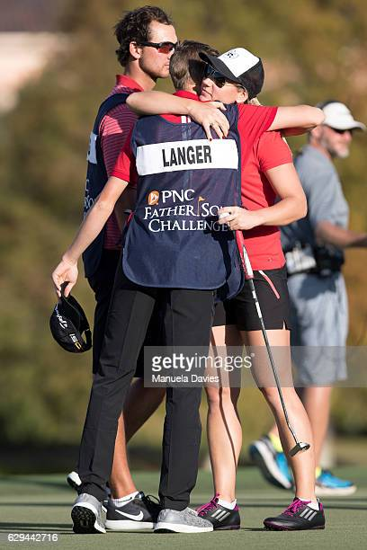 Jason and Christina Langer of Germany hug on the 18th green after the first round of the PNC Father/Son Challenge at The RitzCarlton Golf Club on...