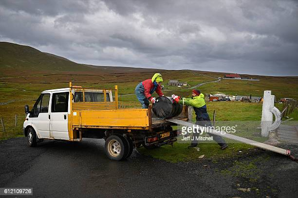 Jason and Stuart Taylor load a tar barrel onto a pick up on the Island of Foula on September 29 2016 in Foula Scotland Foula is the remotest...