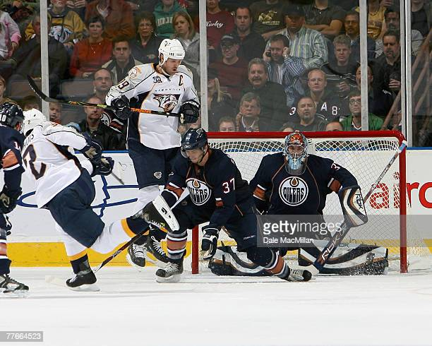 Jason Anott of the Nashville Predators jumps out of the way of the shot of teammate Dan Hamhuis of the Nashville Predators as Denis Grebeshkov and...