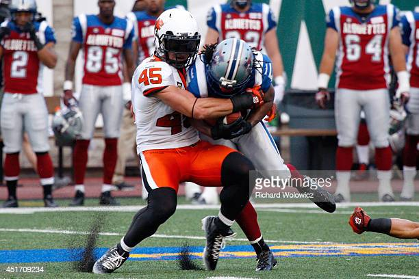 Jason Arakgi of the BC Lions stops Larry Taylor of the Montreal Alouettes during the CFL game at Percival Molson Stadium on July 4 2014 in Montreal...