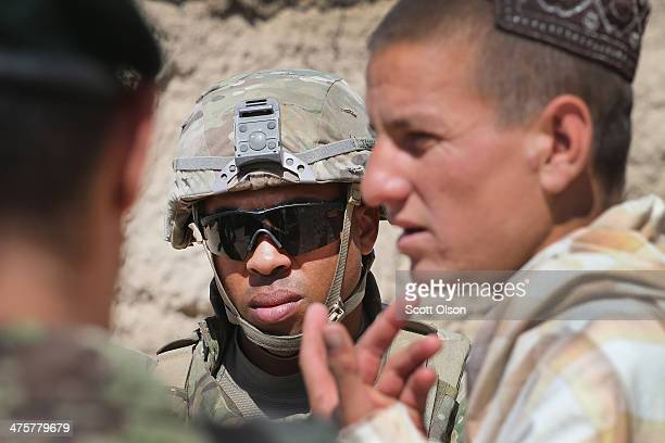 Jason Armstrong from San Jose California with the US Army's 4th squadron 2d Cavalry Regiment questions a resident during a joint patrol through a...