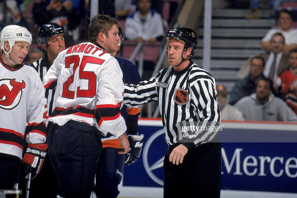 Jason Arnott #25 of the New Jersey Devils gets held by NHL linesman Stephane Provost after an altercation during a game against the New York Islanders at Continental Airlines Arena on September 27, 1999 in East Rutherford, New Jersey. The Devils won 4-3.