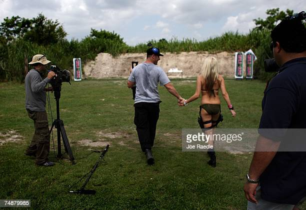 Jason Atkins creator/producer holds the hand of Andrea Brooke Ownbey as they walk to a spot where she will fire her weapon on the set of Girls and...