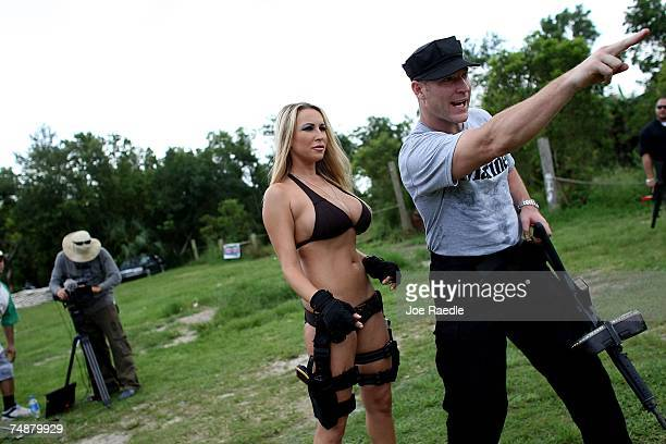 Jason Atkins creator/producer shows Michelle Janetis what target she is to shoot at on the set of Girls and Guns a webbased reality show featuring...