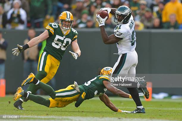 Jason Avant of the Philadelphia Eagles catches a pass in front of AJ Hawk and Tramon Williams of the Green Bay Packers at Lambeau Field on November...