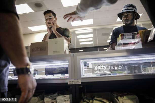 Jason Ayala left and Taylor Anthony right react to the wide variety of pot products sold at 420 Central in Santa Ana Calif on Jan 1 2018 The state...