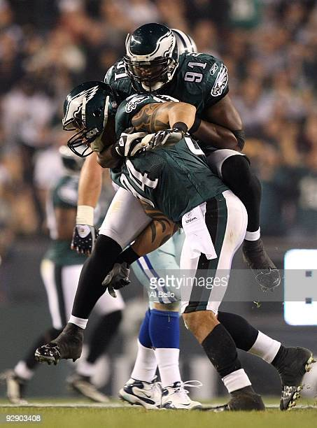 Jason Babin and Chris Clemons of the Philadelphia Eagles celebrate after Babin sacked quarterback Tony Romo of the Dallas Cowboys in the second...
