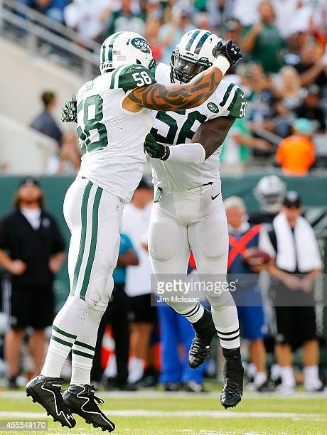 Jason Babin and Demario Davis of the New York Jets celebrate against the Oakland Raiders on September 7 2014 at MetLife Stadium in East Rutherford...