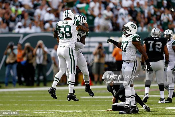 Jason Babin and Demario Davis of the New York Jets celebrate sacking Derek Carr of the Oakland Raiders during the fourth quarter at MetLife Stadium...