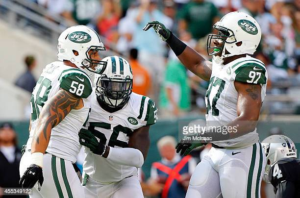 Jason Babin Demario Davis and Calvin Pace of the New York Jets celebrate against the Oakland Raiders on September 7 2014 at MetLife Stadium in East...