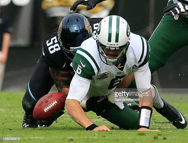 Jason Babin of the Jacksonville Jaguars forces Mark Sanchez of the New York Jets to fumble during the game at EverBank Field on December 9 2012 in...