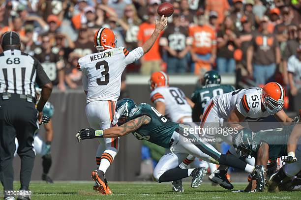 Jason Babin of the Philadelphia Eagles hits Brandon Weeden of the Cleveland Browns at Cleveland Browns Stadium on September 9 2012 in Cleveland Ohio...