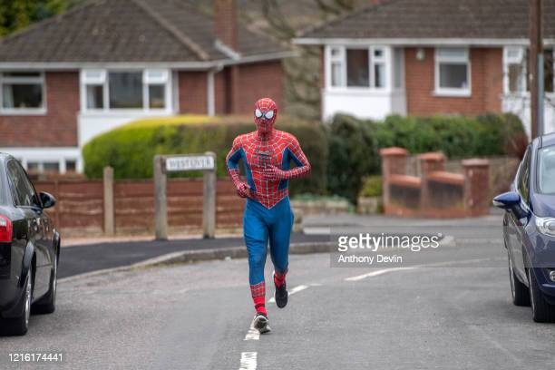 Jason Baird dressed as Spider-Man walks the streets of Bredbury to cheer-up children self isolating at home on April 01, 2020 in Stockport, United...