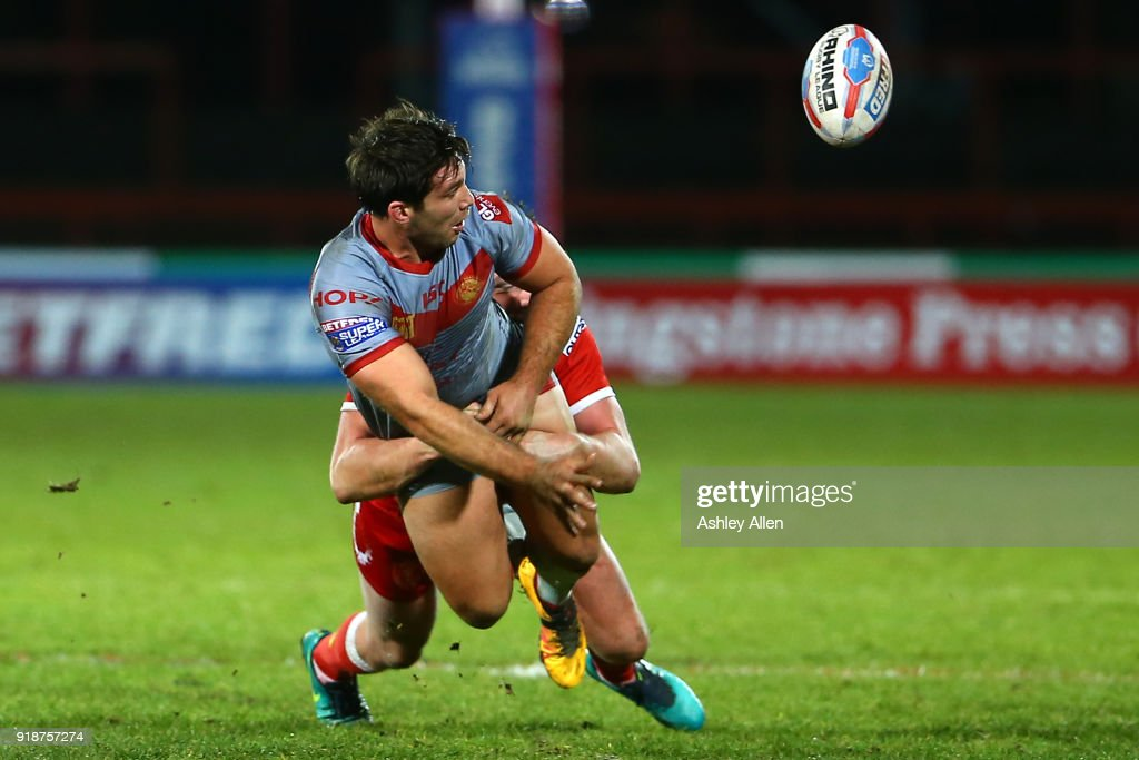 Jason Baitieri of the Catalans Dragons flicks the ball on to a team mate as Liam Salter of Hull KR tackles him during the BetFred Super League match between Hull KR and Catalans Dragons at KCOM Craven Park on February 15, 2018 in Hull, England.