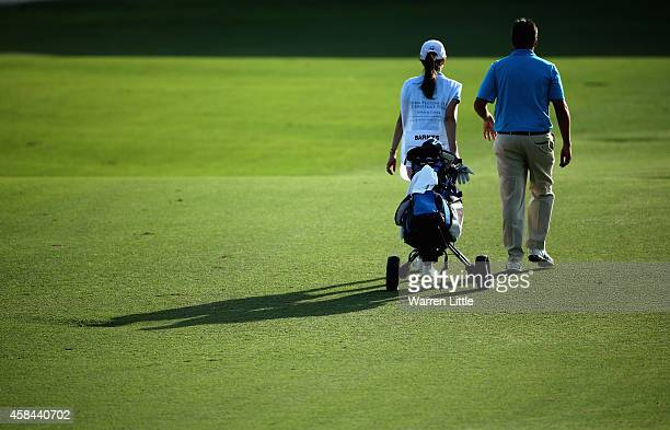 Jason Barnes of England walks with his girlfriend and caddie during the first round of the Dubai Festival City Challenge Tour Grand Final at Al Badia...