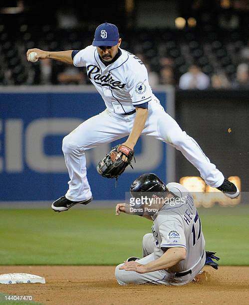 Jason Bartlett of the San Diego Padres jumps over Todd Helton of the Colorado Rockies as he breaks up a double play during the eighth inning of a...