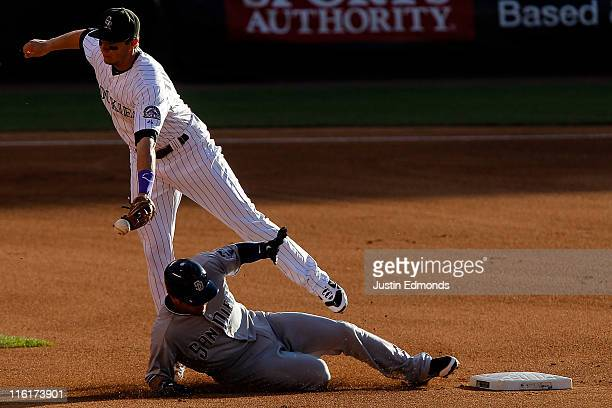 Jason Bartlett of the San Diego Padres slides safely into second base as shortstop Troy Tulowitzki of the Colorado Rockies can't control the ball...