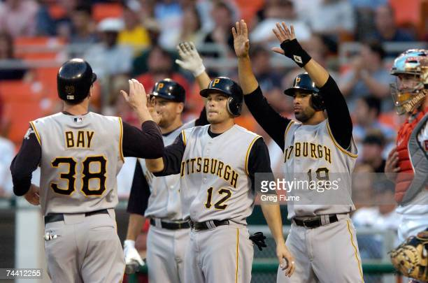 Jason Bay of the Pittsburgh Pirates is congratulated by Freddy Sanchez and Jose Bautista after they all scored on a double by Xavier Nady in the...