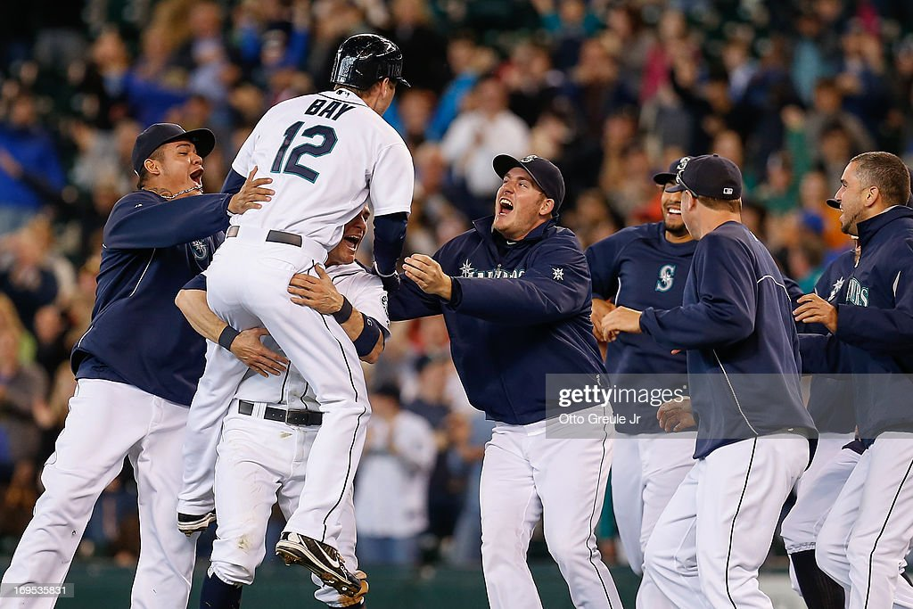 Jason Bay #12 of the Seattle Mariners is congratulated by teammates after getting the game-winning hit in the thirteenth inning to defeat the Texas Rangers 4-3 at Safeco Field on May 26, 2013 in Seattle, Washington.