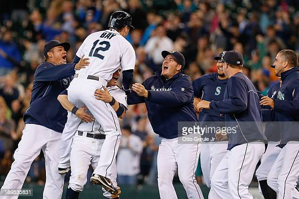 Jason Bay of the Seattle Mariners is congratulated by teammates after getting the gamewinning hit in the thirteenth inning to defeat the Texas...
