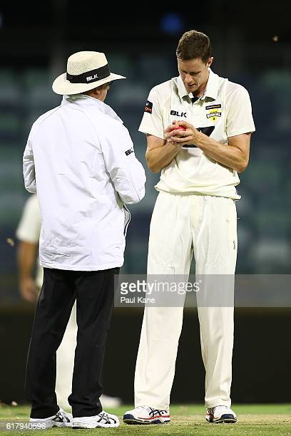 Jason Behrendorff of the Warriors inspects the ball with an umpire during day one of the Sheffield Shield match between Western Australia and South...
