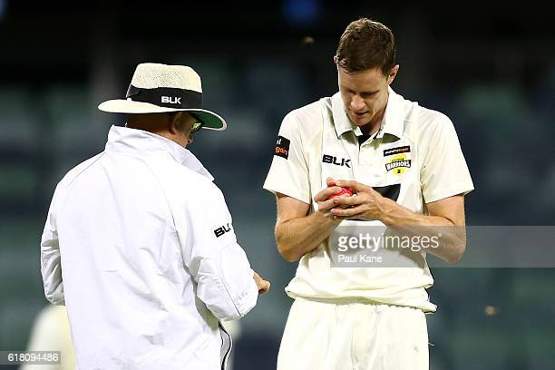 Jason Behrendorff of the Warriors inspects the ball with umpire Ashley Barrow during day one of the Sheffield Shield match between Western Australia...