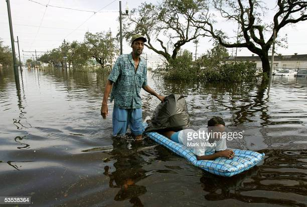 Jason Biggs pushes his wife Diane on a raft down Canal Street, flooded by Hurricane Katrina, August 30, 2005 in New Orleans, Louisiana. Sixty people...