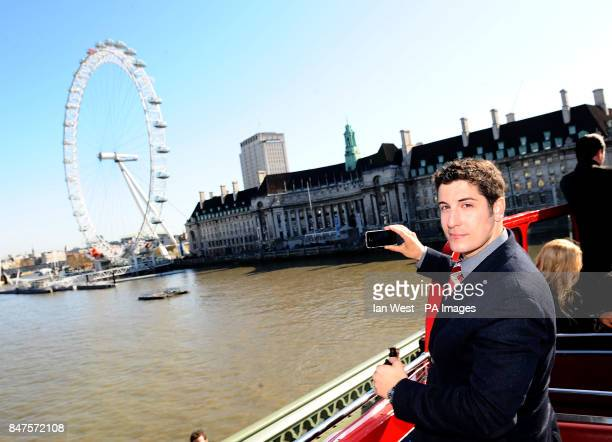 Jason Biggs takes photos of the London Eye while on an open top bus to promote his new film American PieReunion in London