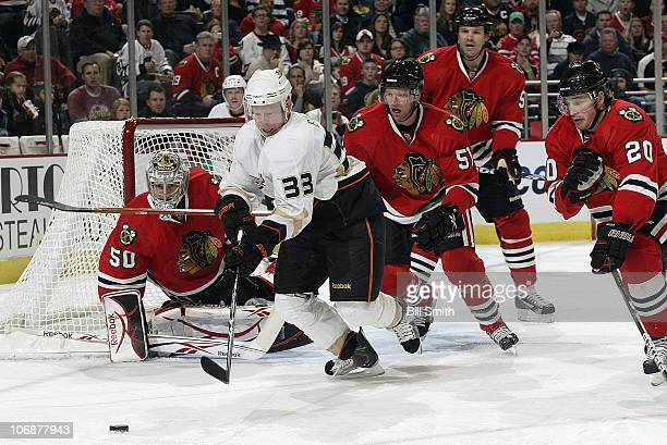 Jason Blake of the Anaheim Ducks reaches toward the puck as goalie Corey Crawford, Brian Campbell, and Jassen Cullimore of the Chicago Blackhawks...