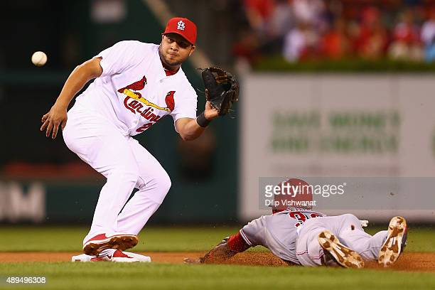Jason Bourgeois of the Cincinnati Reds slides in to second against Jhonny Peralta of the St Louis Cardinals on a wild pitch in the first inning at...