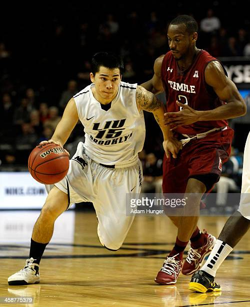 Jason Brickman of the LIU Brooklyn Blackbirds drives to the basket past Will Cummings of the Temple Owls during the Brooklyn Hoops Holiday...