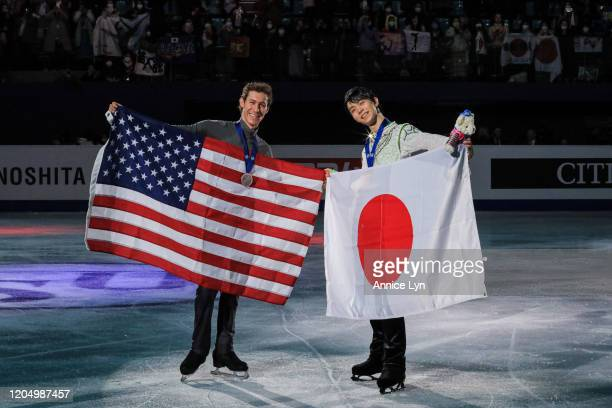 Jason Brown of the United States and Yuzuru Hanyu of Japan pose with their medals and national flags at the Men Free Skating victory ceremony during...