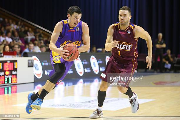Jason Cadee of the Kings takes the ball past Adam Gibson of the Bullets during the Australian Basketball Challenge match between Brisbane Bullets and...