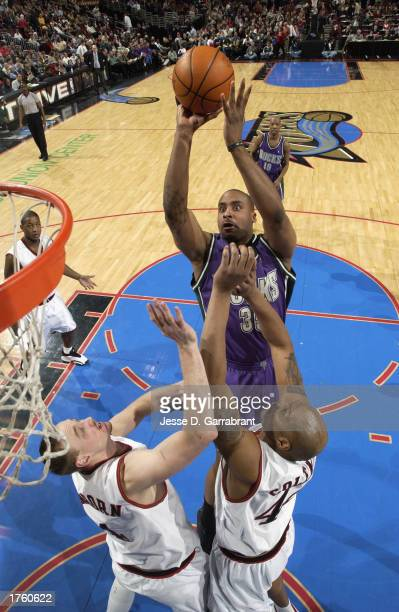 Jason Caffey of the Milwaukee Bucks shoots over Keith Van Horn and Derrick Coleman of the Philadelphia 76ers during the game at First Union Center on...