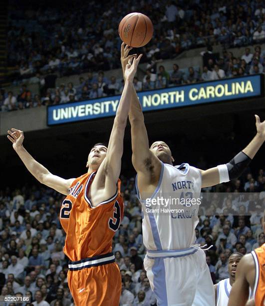 Jason Cain of the Virginia Cavaliers battles Sean May of the North Carolina Tar Heels for a rebound during the first half of an Atlantic Coast...