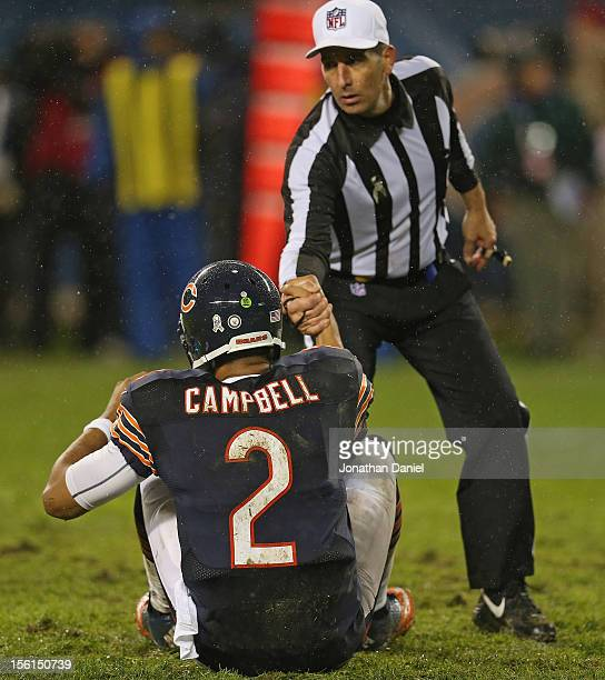 Jason Campbell of the Chicago Bears gets helped up by referee Gene Steratore during a game against the Houston Texans at Soldier Field on November...