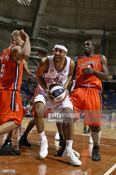 Jason Capel of the Fayetteville Patriots drives against Cournteny James and Ezra Williams of the Columbus Riverdragons December 12, 2003 at the Crown...