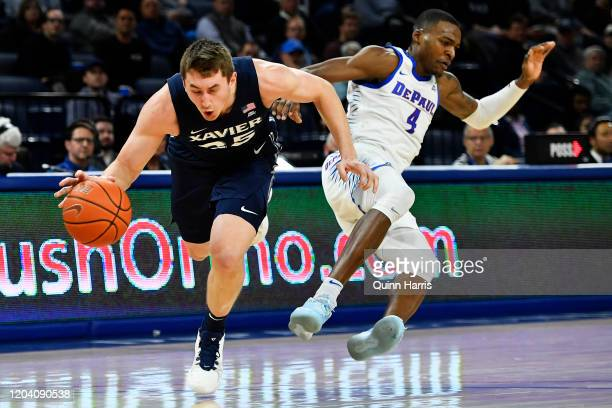 Jason Carter of the Xavier Musketeers falls after being fouled in the first half against Tyrique Jones of the Xavier Musketeers at Wintrust Arena on...