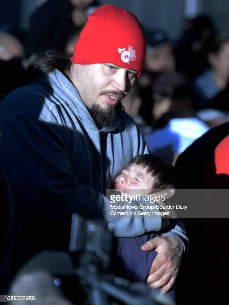 Jason Casias of Fort Collins holds his crying son Seth Casias during a candlelight vigil for Carlos Bustillos at 110 Bowen St in Longmont on Thursday...