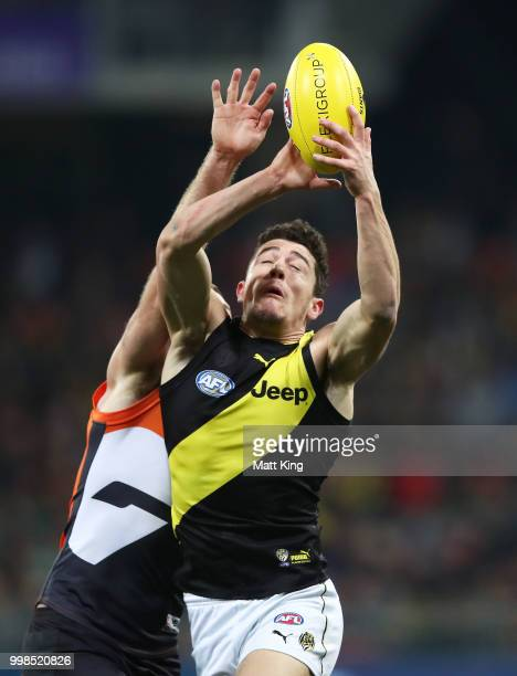 Jason Castagna of the Tigers is challenged by Heath Shaw of the Giants during the round 17 AFL match between the Greater Western Sydney Giants and...
